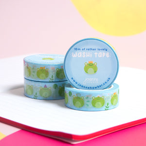 A stack of blue and green frog washi tape piled on top of a notebook with one roll facing forwards to show the decorative sticker.