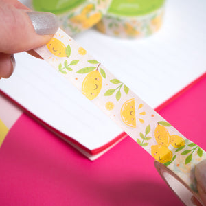 Lemon washi tape being peeled off of the roll by a pair of hands over a pink background with a white notebook.