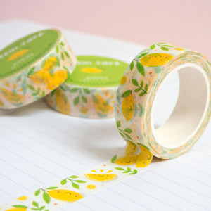 A roll of lemon washi tape unravelling on a notebook with stacks of paper tape in the background.
