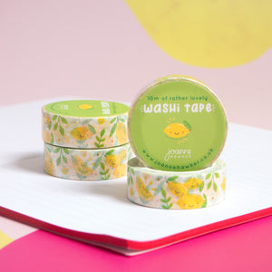 Rolls of lemon washi tape stacked up onto of each other with one roll facing the camera to show the sticker. The washi tape is sat on a notebook and a pink background