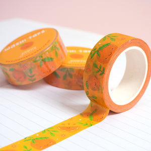 A roll of orange satsuma washi tape unravelling on a notebook with stacks of paper tape in the background.