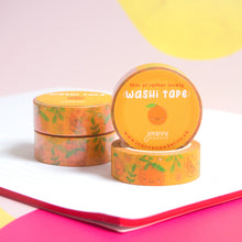 Load image into Gallery viewer, A stack of orange satsuma washi tape piled on top of a notebook with one roll facing forwards to show the decorative sticker.