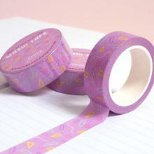 Load image into Gallery viewer, A roll of purple confetti washi tape unravelling on a notebook with stacks of paper tape in the background.