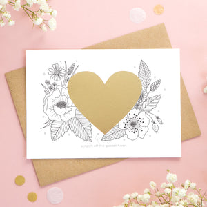 A personalised wedding scratch card shot on a pink background with white flowers. The golden heart is unscratched showing how the card will arrive.