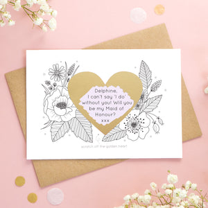A personalised wedding scratch card shot on a pink background with white flowers. The golden heart has been scratched revealing a purple heart and a maid of honour proposal!