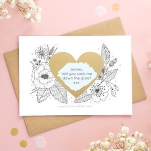 A personalised wedding scratch card shot on a pink background with white flowers. The golden heart has been scratched revealing a blue heart and a proposal asking to be walked down the aisle!
