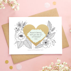 A personalised wedding scratch card shot on a pink background with white flowers. The golden heart has been scratched revealing a green heart and a witness proposal!