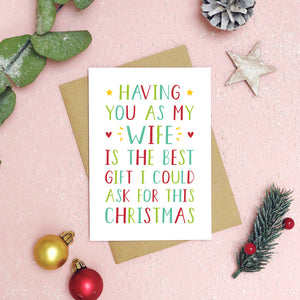 A 'best gift' wife Christmas card has been shot on a pink background with foliage, baubles and Christmas props surrounding the card. The writing on the card is red and green.