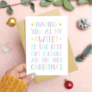 A 'best gift' wife Christmas card held over a pink background by a hand in a mustard knit jumper with foliage and baubles in the background. The writing on the card is blue and pink