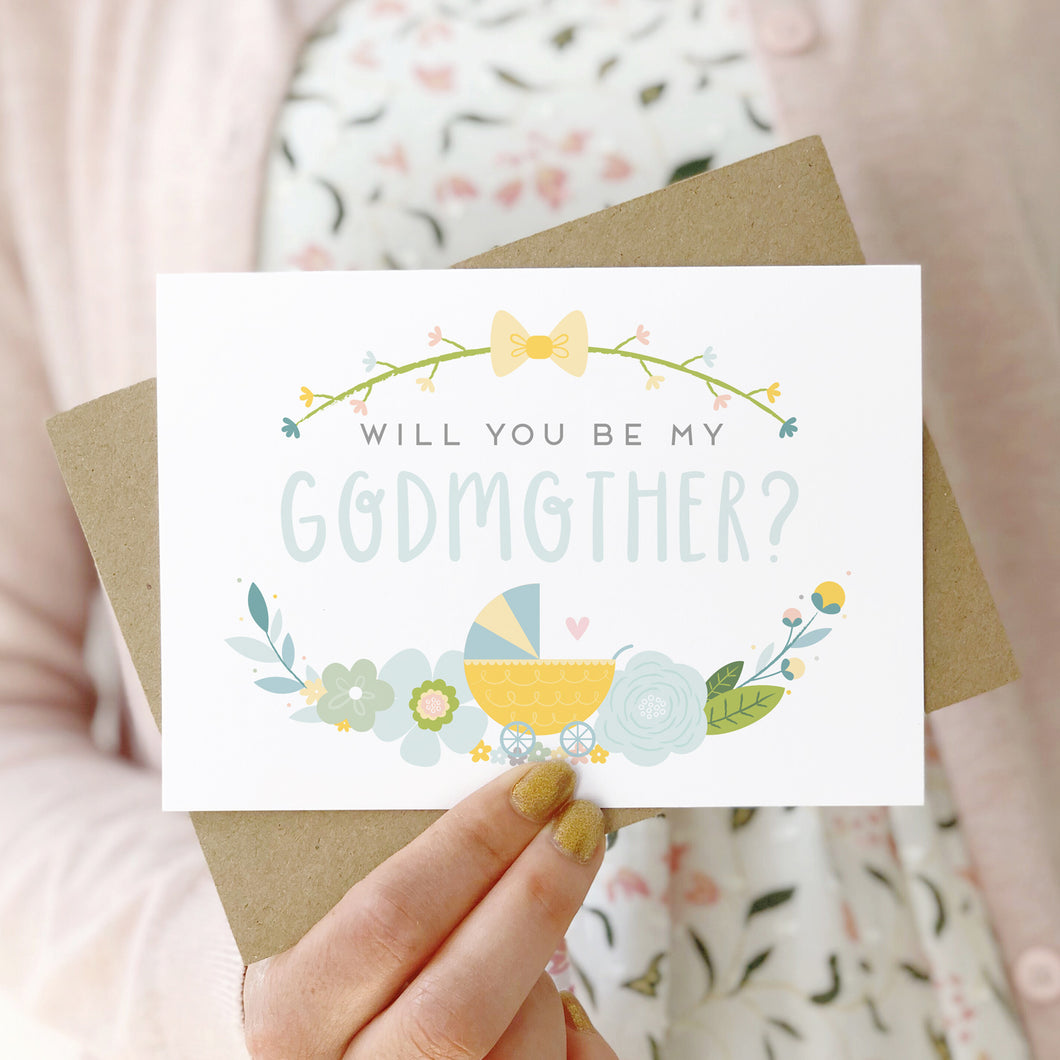A will you be my godmother card being held in front of a white dress and pink cardigan. The design features a pram, simple florals and the all important question. This is the blue palette.