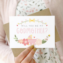 Load image into Gallery viewer, A will you be my godmother card being held in front of a white dress and pink cardigan. The design features a pram, simple florals and the all important question. This is the pink palette.