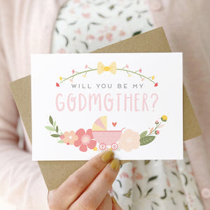 A will you be my godmother card being held in front of a white dress and pink cardigan. The design features a pram, simple florals and the all important question. This is the pink palette.