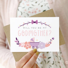 Load image into Gallery viewer, A will you be my godmother card being held in front of a white dress and pink cardigan. The design features a pram, simple florals and the all important question. This is the purple palette.