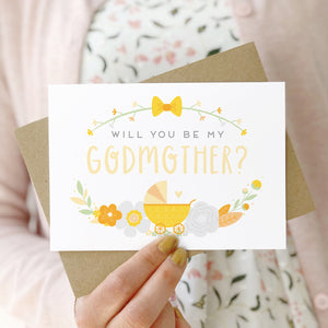 A will you be my godmother card being held in front of a white dress and pink cardigan. The design features a pram, simple florals and the all important question. This is the yellow palette.