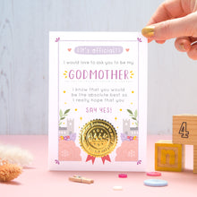 Load image into Gallery viewer, A will you be my Godmother certificate card in pink and purple, shot on a pink and grey background with a hand coming in from the top right. There are dry flowers, buttons and building blocks in the foreground.
