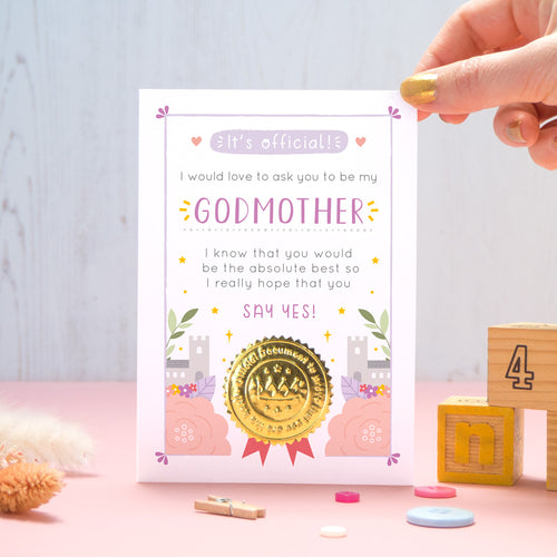 A will you be my Godmother certificate card in pink and purple, shot on a pink and grey background with a hand coming in from the top right. There are dry flowers, buttons and building blocks in the foreground.
