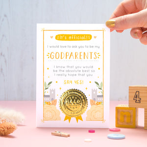 A will you be my Godparents certificate card in orange, shot on a pink and grey background with a hand coming in from the top right. There are dry flowers, buttons and building blocks in the foreground.