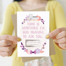 Load image into Gallery viewer, A will you be my godparents scratch and reveal card being held in front of a white dress and yellow cardigan. The design features a church, simple florals and a scratch off panel in silver. This is the purple palette.