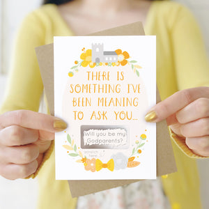 A will you be my godparents scratch and reveal card being held in front of a white dress and yellow cardigan. The design features a church, simple florals and a scratch off panel in silver. This is the yellow palette.