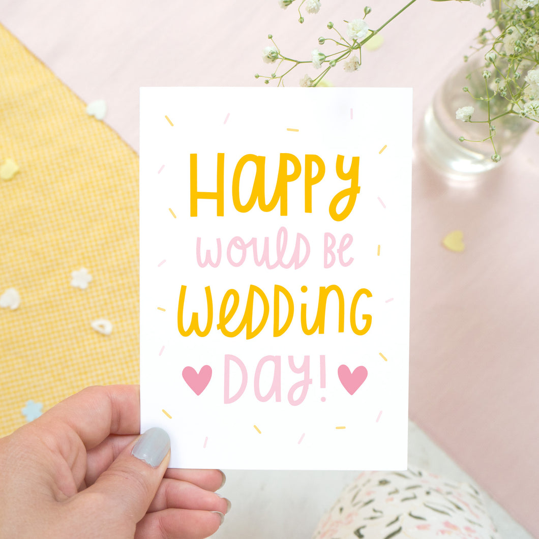 Happy would be wedding day card in orange and pink photographed in a hand against a pink, and yellow background with a hint of flowers.