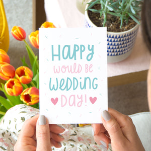 Happy would be wedding day card in teal and pink. Photographed in a lifestyle setting being held over a lap with tulips and a succulent in the background.