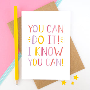 You can do it, I know you can! - Positive encouragement card photographed on a pick and white background separated with a teal ribbon. Also featuring a yellow pencil for scale. This version is in pink, yellow and lilac colour palette.