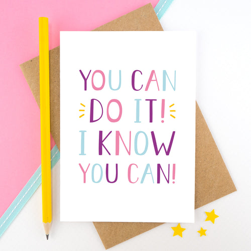 You can do it, I know you can! - Positive encouragement card photographed on a pick and white background separated with a teal ribbon. Also featuring a yellow pencil for scale. This version is in pink, purple and blue colour palette.