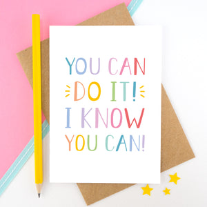 You can do it, I know you can! - Positive encouragement card photographed on a pick and white background separated with a teal ribbon. Also featuring a yellow pencil for scale. This version is in a rainbow colour palette.
