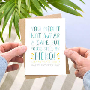 A hero father's day card in tones of blue and a pop of yellow photographed being held by a man over a grey stripy rug, blue floor and a leafy plant.