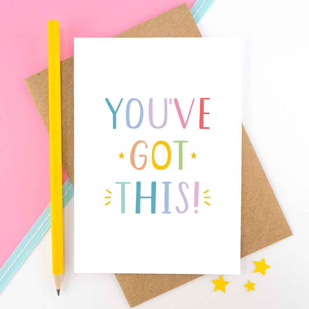 You've got this! A positive encouragement card photographed on a pink and white background with a teal ribbon and bright yellow pencil. The lettering on this card is in rainbow tones.