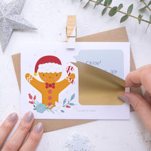 Load image into Gallery viewer, A personalised gingerbread man scratch card where the sticking down of the gold scratch panel is being demonstrated. Shot on a white background with a glittery star and sprig of eucalyptus.