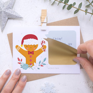 A personalised gingerbread man scratch card where the sticking down of the gold scratch panel is being demonstrated. Shot on a white background with a glittery star and sprig of eucalyptus.
