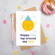 Load image into Gallery viewer, An any age birthday card featuring a happy sun in a party hat and text that reads 'Happy 12th lap around the sun'. This card has been photographed on a grey background surrounded by a cupcake, pen and confetti.