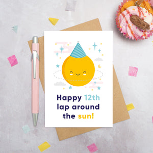 An any age birthday card featuring a happy sun in a party hat and text that reads 'Happy 12th lap around the sun'. This card has been photographed on a grey background surrounded by a cupcake, pen and confetti.