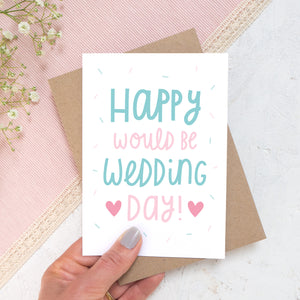 Happy would be wedding day card in teal and pink photographed in a hand against a pink, and white background with a hint of flowers.