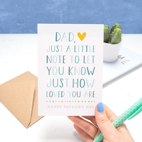 A father's day card by Joanne Hawker being held in her right hand, with a green pen on a white and blue background. The card reads