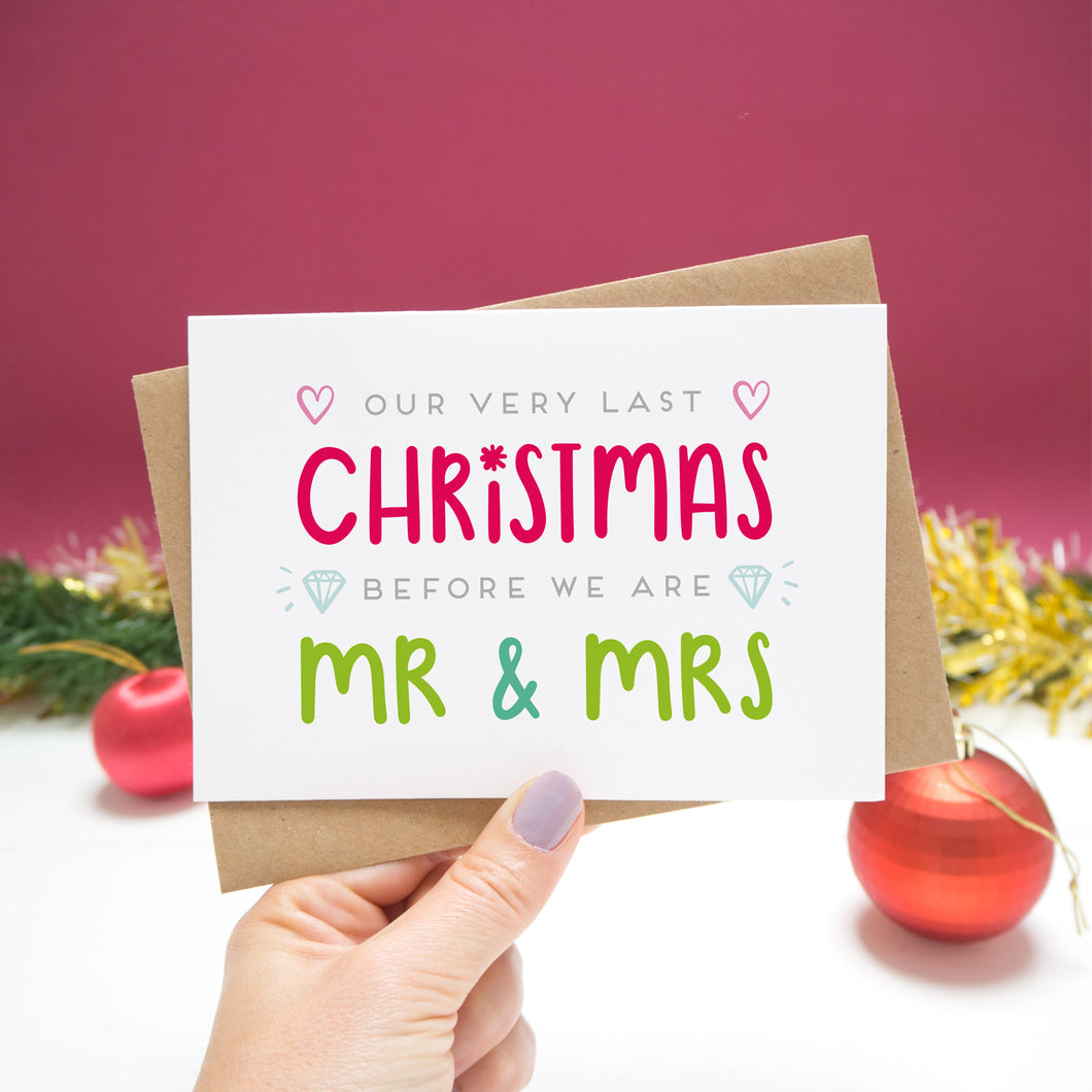 'Our very last Christmas before we are Mr and Mrs. Christmas Card held in front of a Christmassy scene with baubles and tinsel.