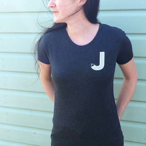 Grey charcoal tshirt with a white letter pencil initial J, modelled by Joanne Hawker in front of a green beach hut.