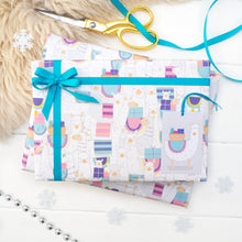 A parade of llama and alpaca wearing a variety of blankets printed onto white gift wrap. Matching fox tag shown on the bottom right of the wrapping paper. The present is strung with turquoise ribbon and features a small bow.