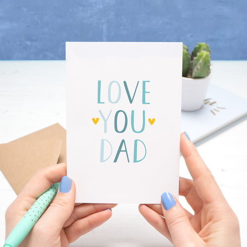 Love you dad card held over a white and blue background by Joanne Hawker in her somerset studio. The text on the card is in varying tones of blue with two yellow hearts surrounding the word 'you'.