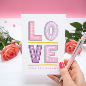 A personalised 'love' card with individual hand drawn letters and the names of the two love birds beneath. Image features the valentines card set on a pink background with roses either side held in the right hand with a pen.