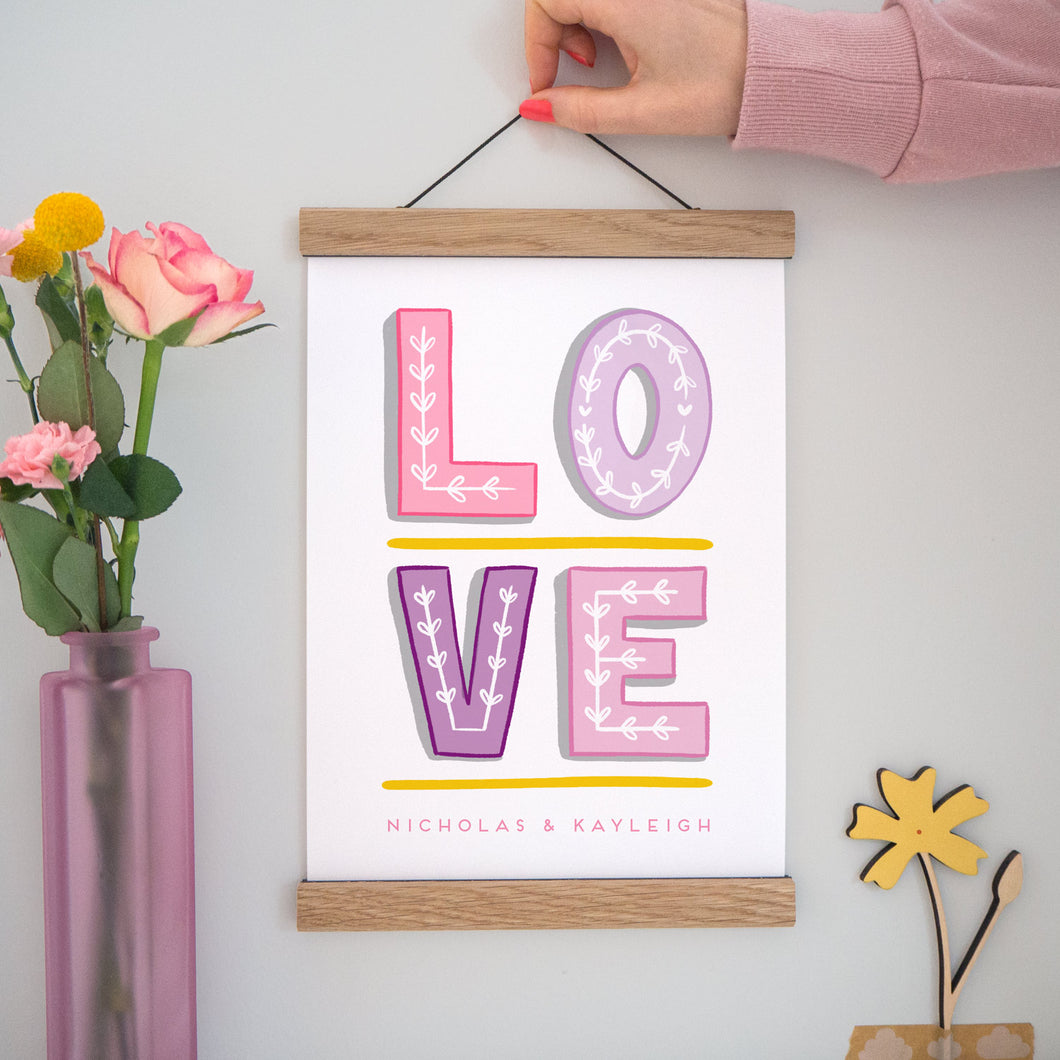 A personalised 'love' print featuring hand drawn typography in varying shades of pink and purple with space for the names of the couple. The image has a vase of flowers to the left, the print being held centre and a small wooden flower in the bottom right set on a grey background.