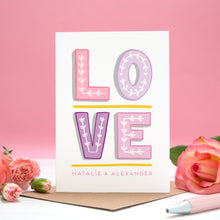Load image into Gallery viewer, A personalised 'love' card with individual hand drawn letters and the names of the two love birds beneath. Image features the valentines card set on a pink background with roses either side.