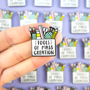 Tools of Mass Creation Pin featuring a pencil case filled with creative tools such as a pencil, wool, knitting needles, paint, a ruler etc.