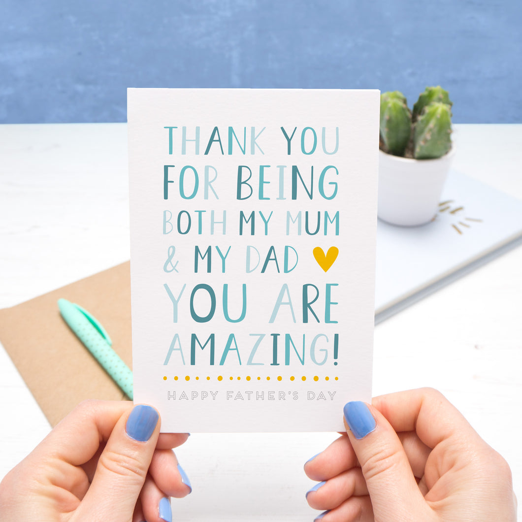 A card for the amazing single parent who plays the role of mum and dad. This image features the card being held by Joanne Hawker on a white and blue background. The card features blue text with a yellow heart.