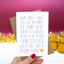"Load image into Gallery viewer, Having you as my Mummy is the best gift I could ask for this Christmas, lots of love from bump."" - Christmas bump card with pink and blue text set on a red background with gold tinsel and mustard shoes."