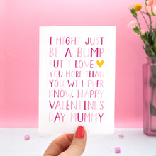 "A valentine's card from the 'bump' with text in different shades of pink that reads ""I might just be a bump but I love you more thank you will ever know. Happy Valentine's day Mummy."" The card is held in one hand and there is a vase of flowers in the pink background."
