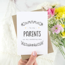 To my parents on my wedding day. A white card with grey hand drawn lettering, and a grey floral border. The image features a wedding dress and bouquet of flowers.