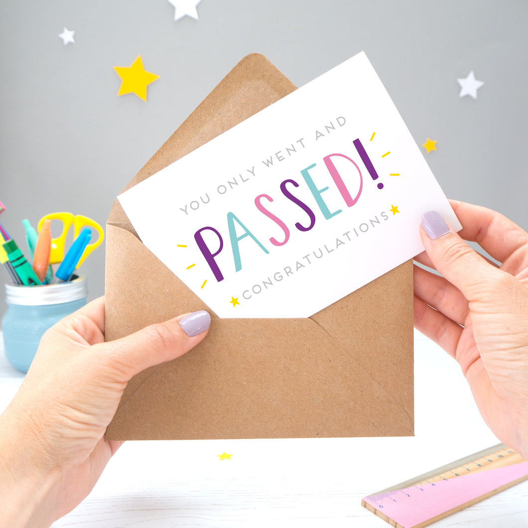 'You only went and passed! Congratulations!' A congratulations card for someone who has completed their exams recently. It features grey text with the word 'passed' in a hand lettered font with varying tones of blue, pink and purple, and yellow stars.