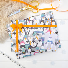 Load image into Gallery viewer, A parade of penguins wearing a variety of Christmas fancy dress printed onto white gift wrap. Matching penguin tag shown on the bottom right of the wrapping paper. The present is strung with orange ribbon and features a small bow.